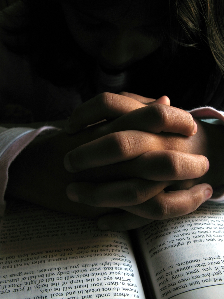 Hands folded in prayer on an open Bible under soft incandescent light