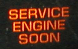 An orange/red 'service engine soon' indicator on a black background