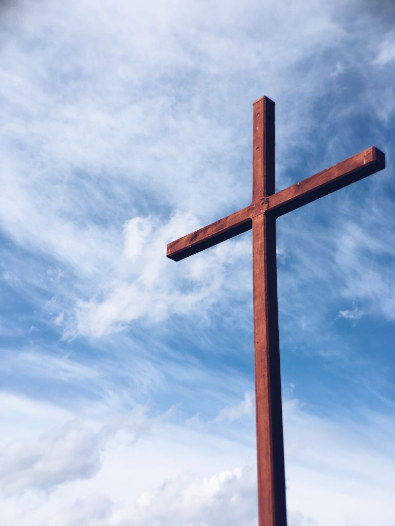 A large red wood cross against a clouded blue sky