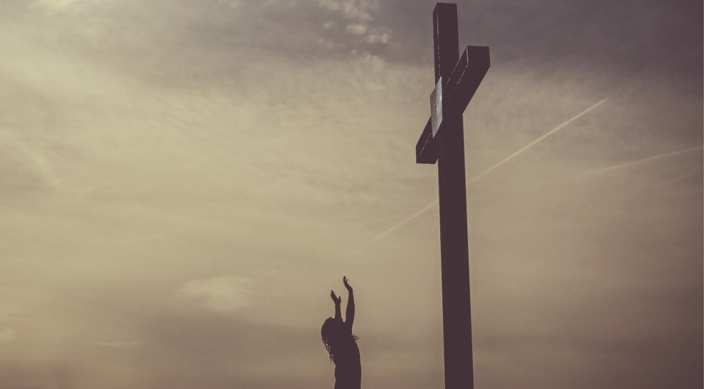 The side view of a woman with arms raised toward a large cross with a hazy cloudy sky in the background