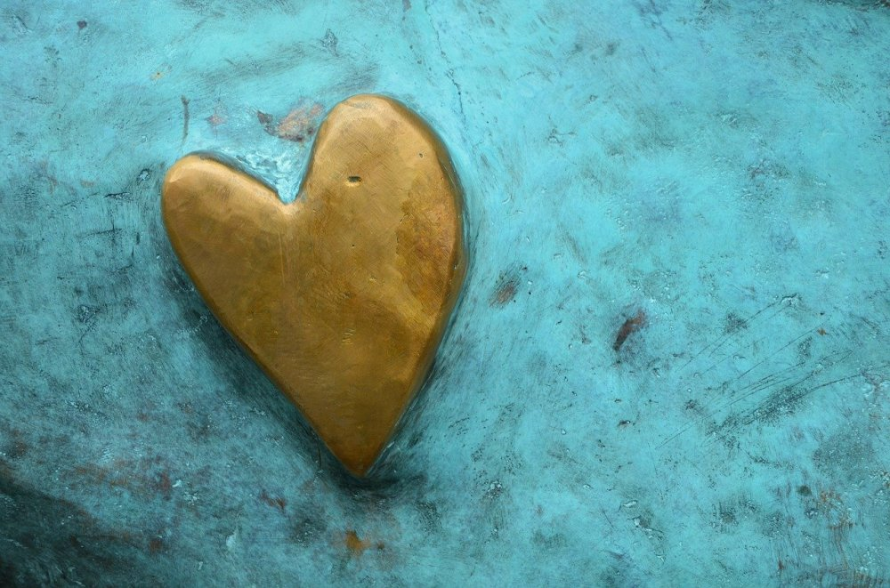 A raised gold painted heart on a turquoise painted stone surface