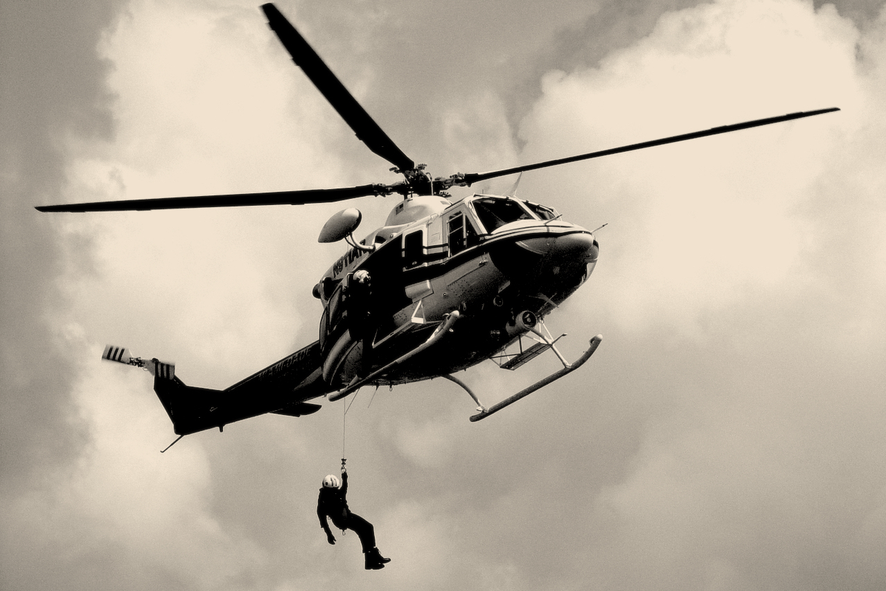 A sepia tinted black and white picture of a man being lowered from a helicopter hovering in the sky with clouds in the background
