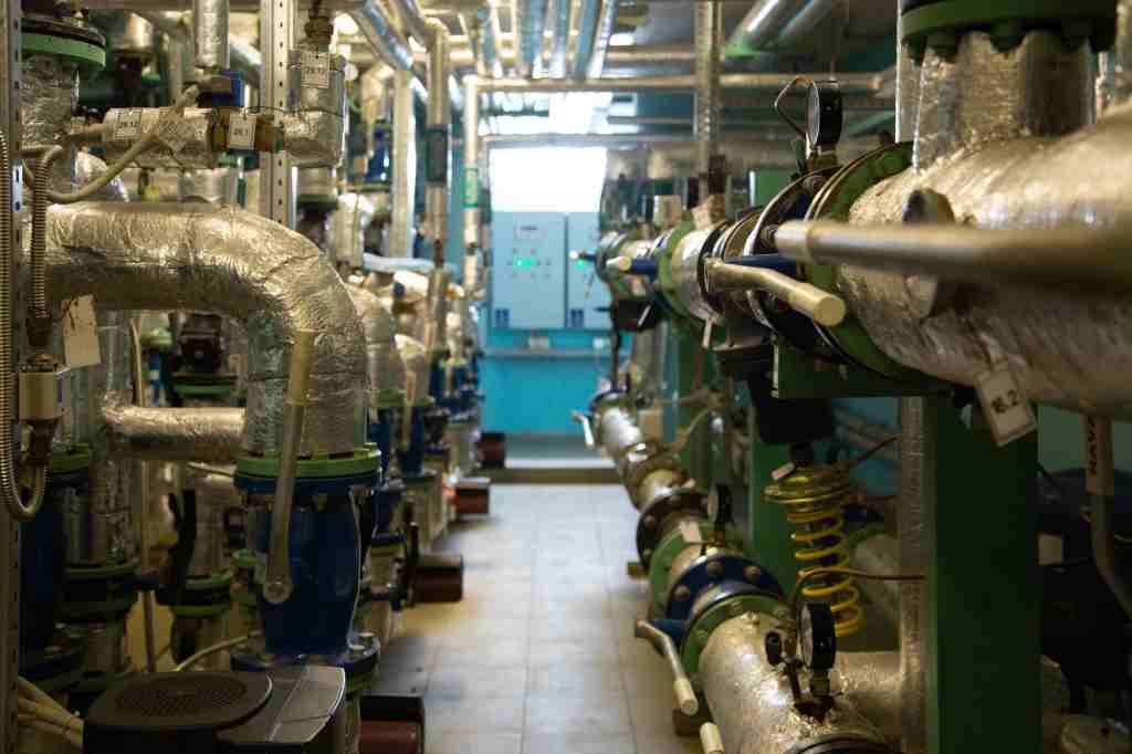 A narrow walkway with various insulated pipes of industrial equipment and control panels at the end of the walk