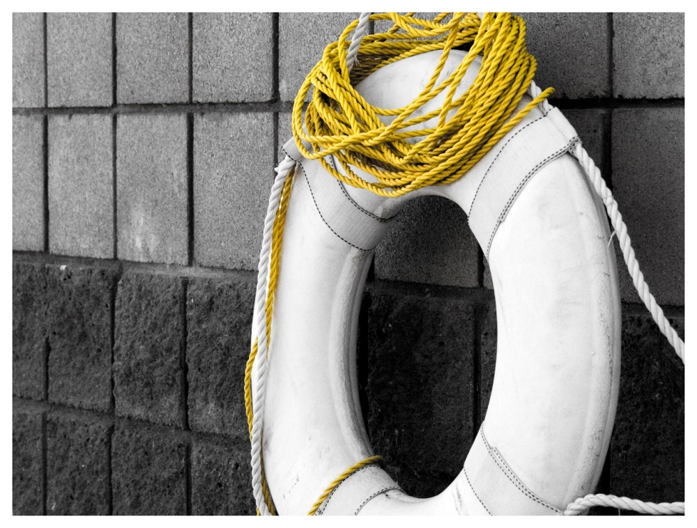 A white life preserver with coil of yellow rope hanging on a black stone tiled wall