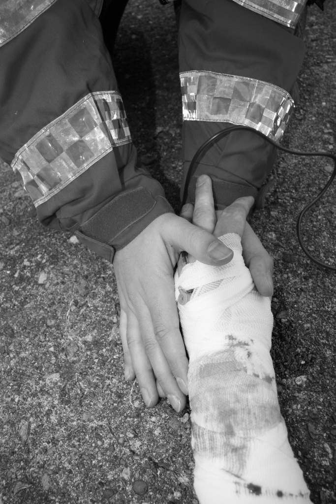 A black and white picture of the hands of a medic holding the bandaged hand of an injured person