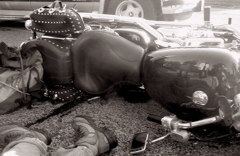 A black and white picture of a wrecked motorcycle lying on its side with the feet and legs of the rider on the ground beside the motorcycle and part of a pickup truck in the background