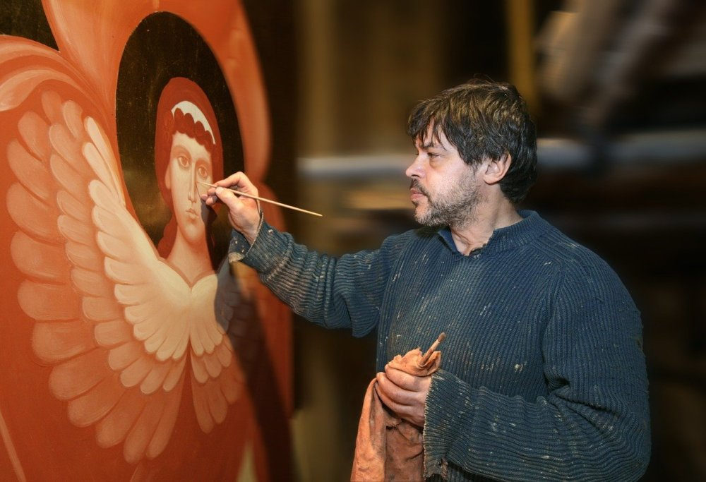 A man painting an angel with various shades of dark orange paint inside a large studio