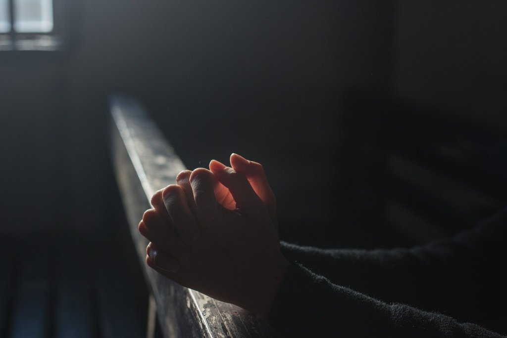 Hands in position of prayer in soft light from nearby window