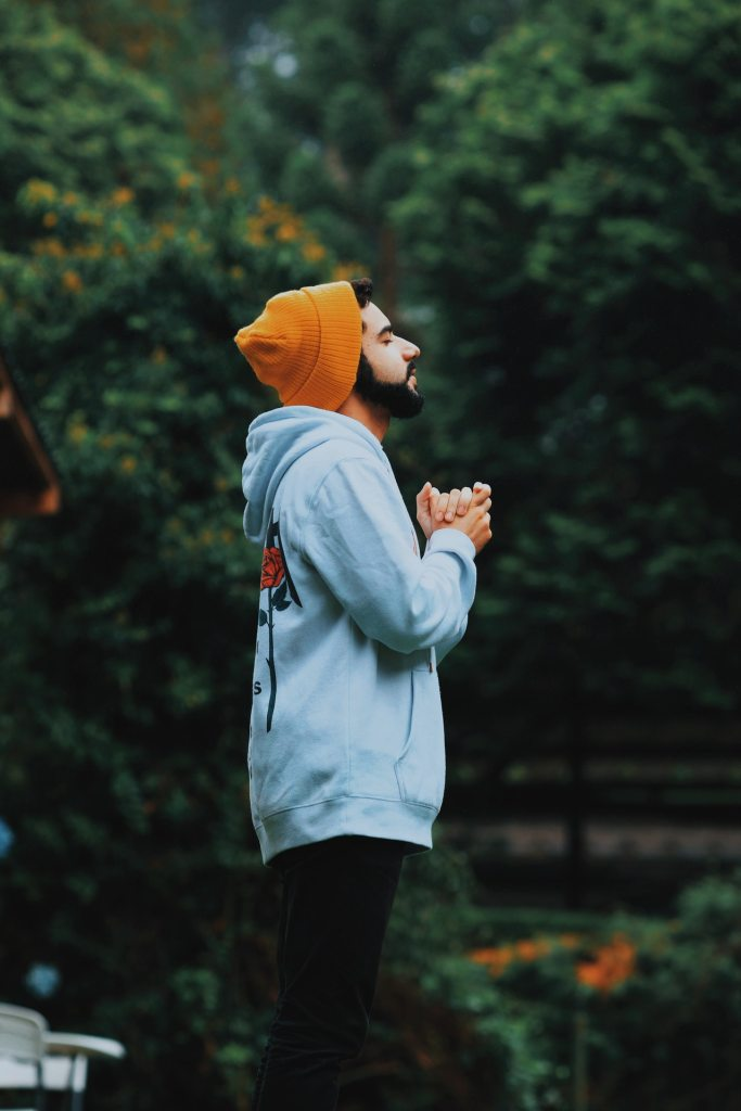 A man with a beard standing and wearing a dark orange knit hat, a light blue hooded sweatshirt and dark blue pants with eyes closed and hands held together in prayer with trees in the background.
