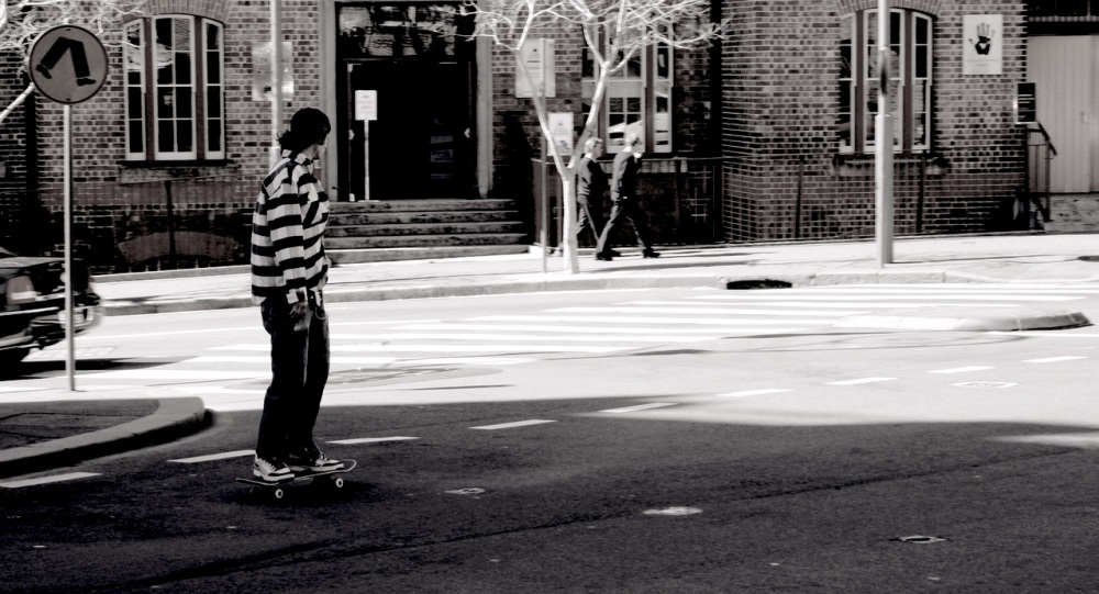 A black and white photo of a young man riding a skateboard into small intersection of a city with a building and two men walking in the background