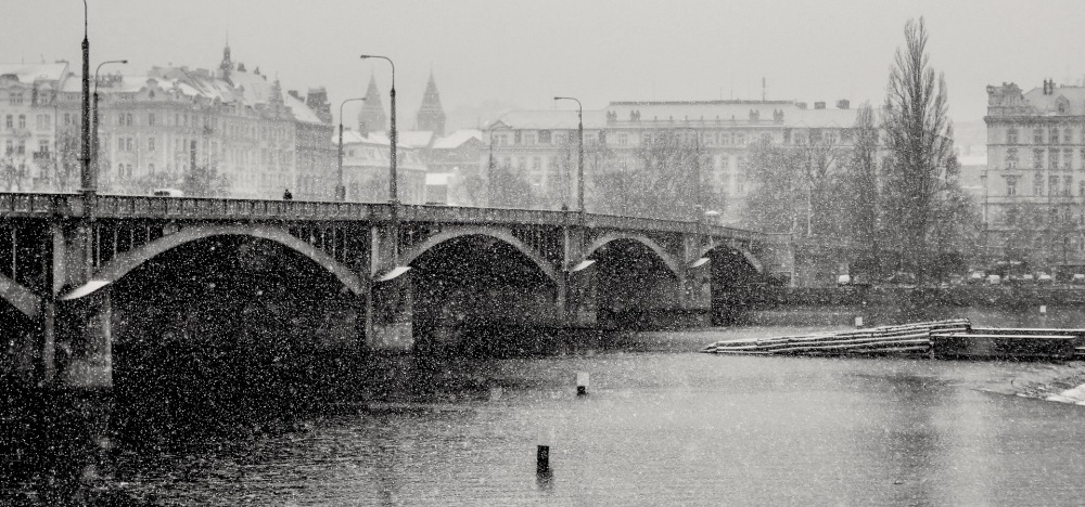 Black and white image of a multi-arched stone bridge over a river on a cloudy, snowy day in a city