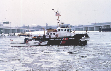 A photograph of the US Coast Guard cutter Capstan in the broken ice filled Potomac River near the 14th Street bridge in Washington, DC on a cloudy day