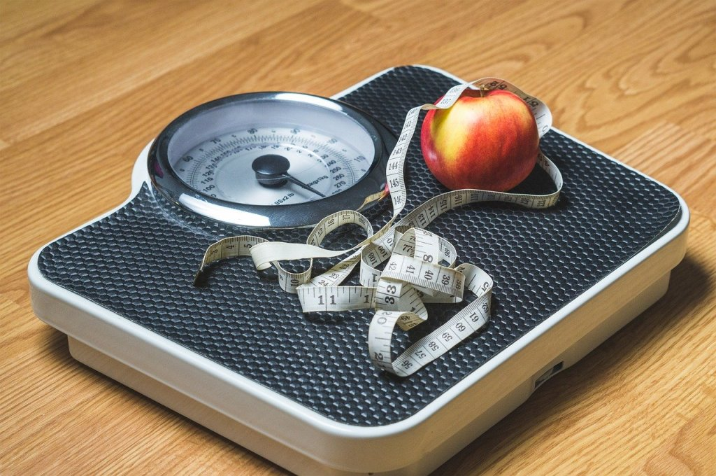 A scale resting on a wooden floor with a tape measure and piece of fruit.