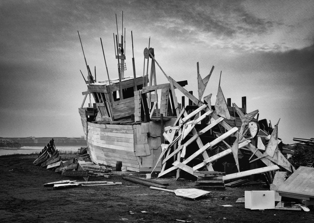 A black and white picture of a completely wrecked wooden fishing vessel on shore