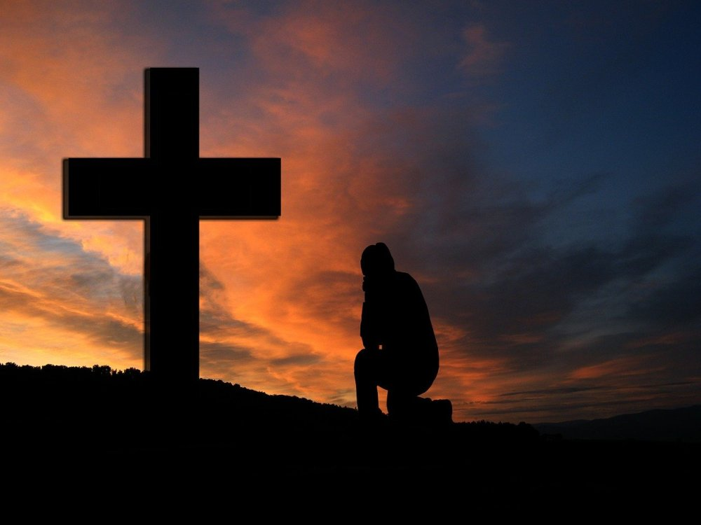 A silhouette of a man kneeling at a large cross with reddish clouds at sunset in the background