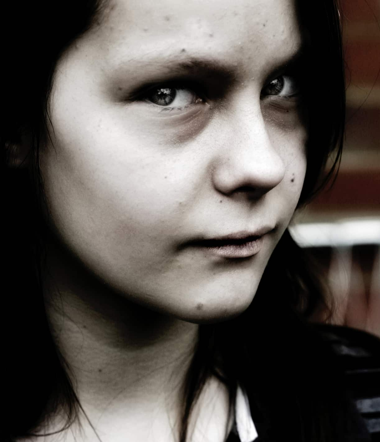 Younger woman facing camera with head turned slightly and expression of warning or evil in eyes
