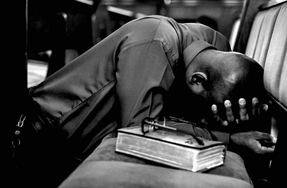 A black and white picture of a man in prayer at a church pew with bible and glasses nearby