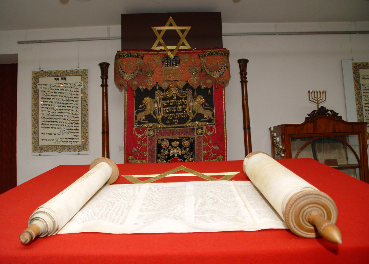 A scroll of the Torah opened on a red table with various Jewish decorum in the background