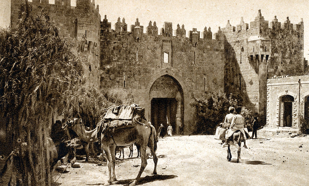 A sepia postcard from the 1920s of the Damascus Gate in Jerusalem with camels and a person on a donkey