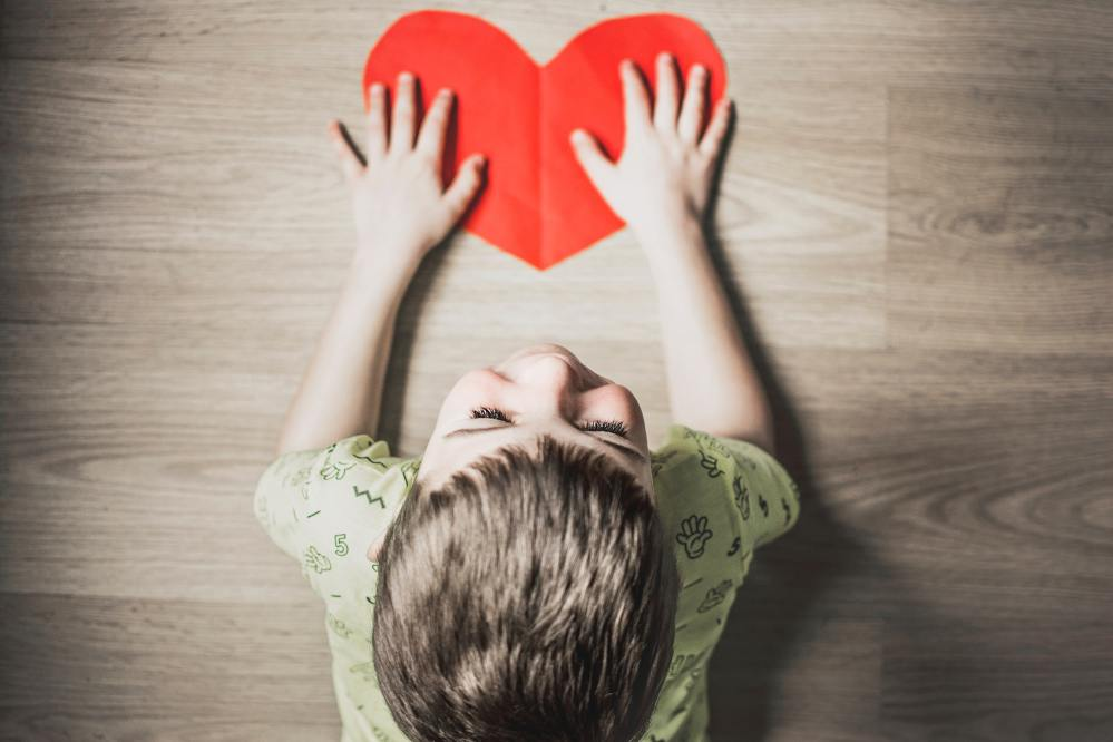 Overhead view of boy in green shirt laying stomach down on floor with hands resting on cut-out of a red paper heart