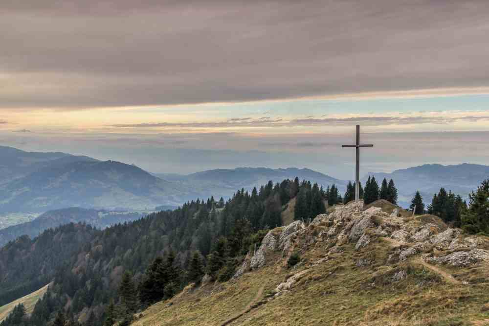 A cross on a rocky hillside in Austria with mountains in the distance and a cloudy pastel sky in the background