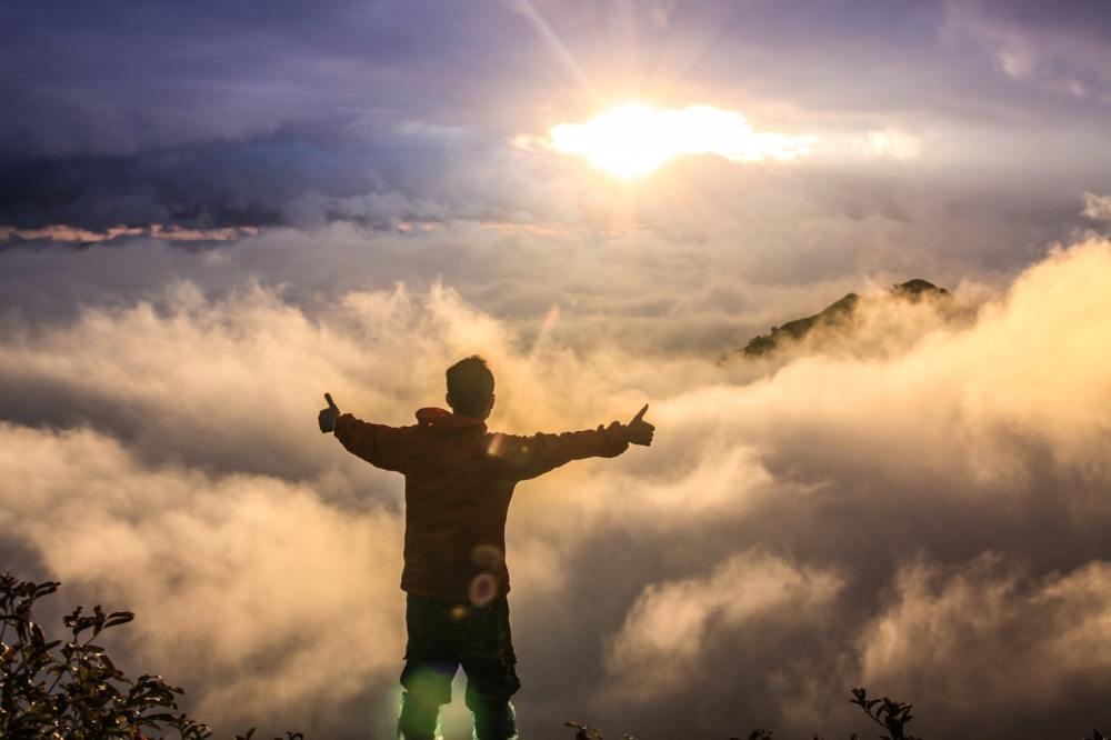 A man standing above the clouds with his arms outstretched and thumbs up with clouds and sun in the distance.