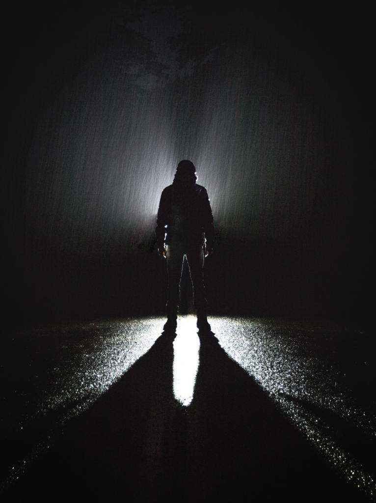 A black and white silhouette of a person in the darkness with a light behind them and rain falling