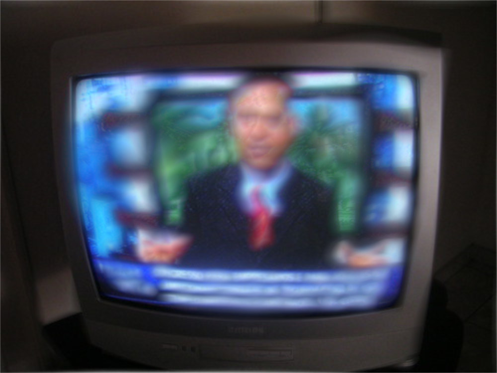 Blurred photo of televangelist on a small television in a room