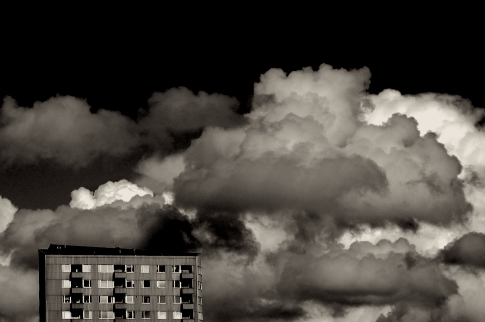 Black and white image of an apartment building in lower left corner and a dense cluster of assorted cumulus clouds behind with a black sky in the background
