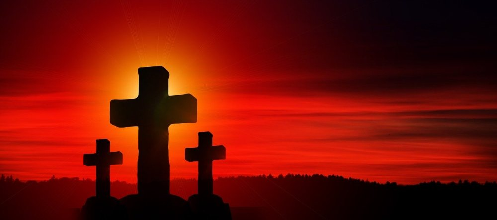 A large stone cross in the middle of two smaller crosses on an elevated hillside with an intense red sky in the background