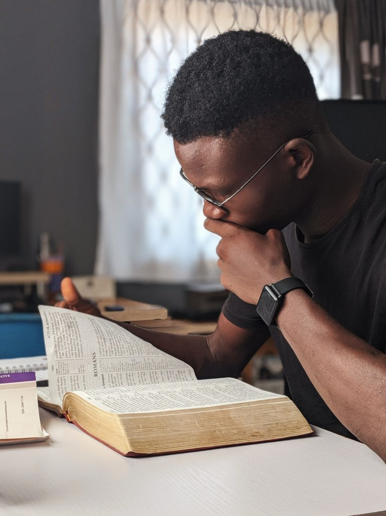 Photo of an African-American man wearing glasses while reading a Bible and holding his left up towards his mouth