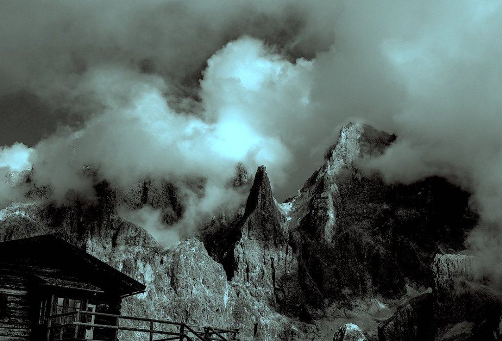 A blue tinted black and white image of a building in the left corner of the foreground with the pale di san martino mountain range in the background