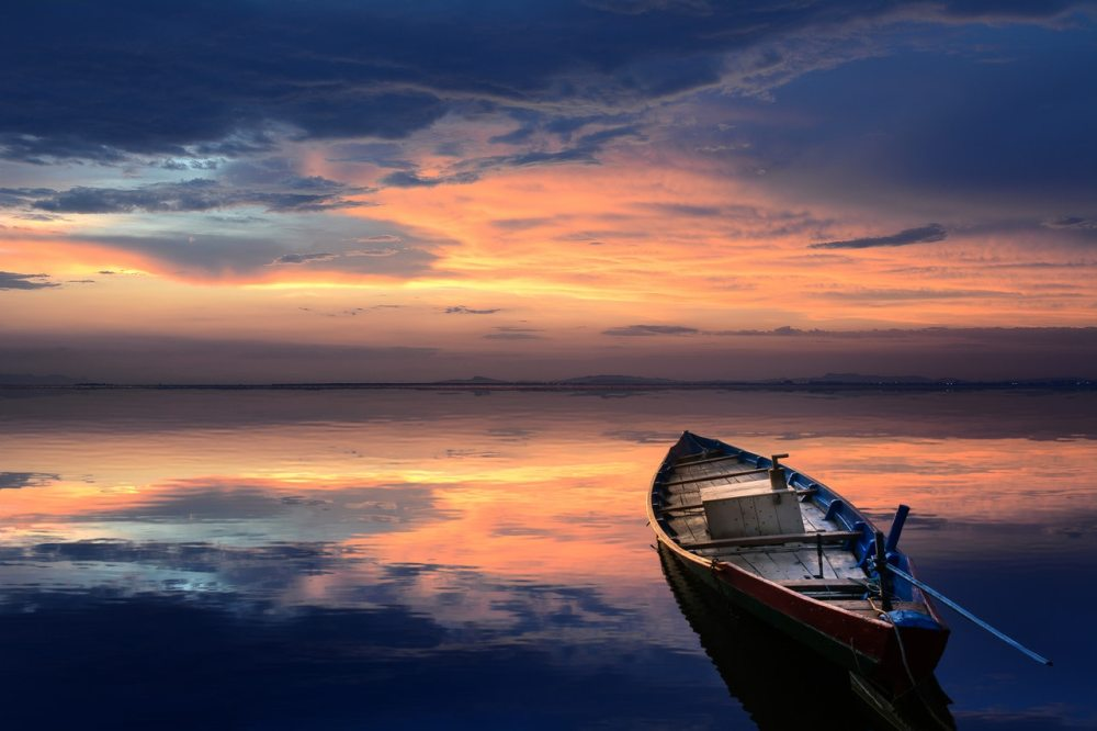 A multicolored sunset sky reflecting on a motionless sea with a small wooden boat pointed outward in the lower right corner