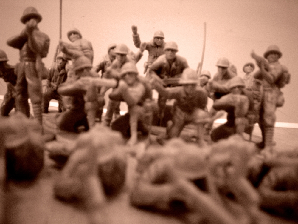 A sepia image of a battalion of toy soldiers standing and kneeling while aiming weapons at another set lying down in the foreground