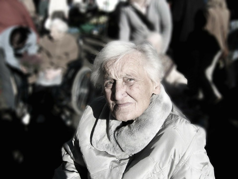 An older woman with white hair wearing a grey winter coat with bright sunlight on her face and looking suspiciously in the direction of the camera with many people in the distant background