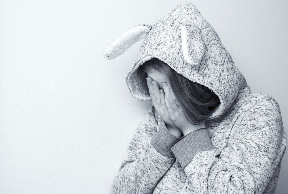 A black and white photo of a girl wearing a hooded sweatshirt with floppy ears and holding her hands over her face