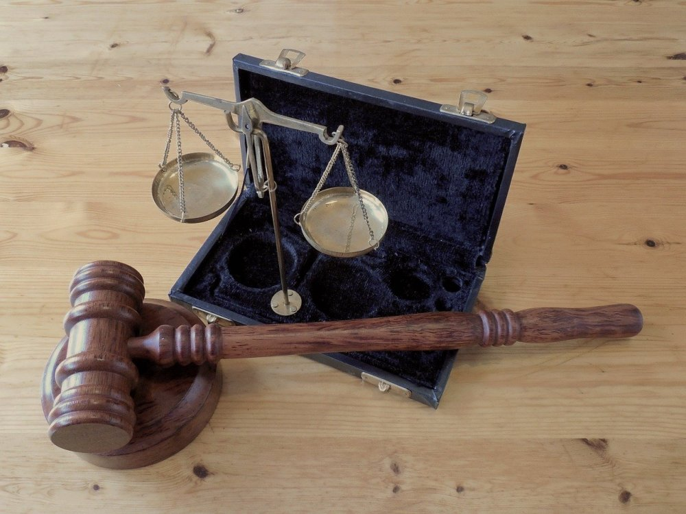 A photo of a wooden gavel and a brass scale of justice set up in its case while resting on a wooden surface.