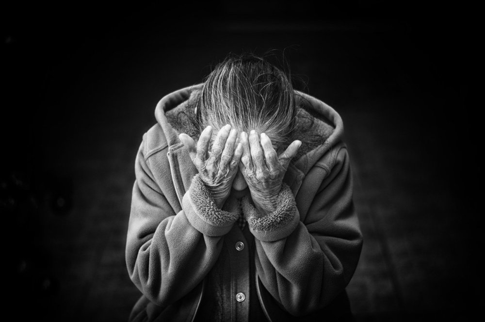 A black and white photo of a solitary older woman wearing a heavy coat with her head leaning down into her hands