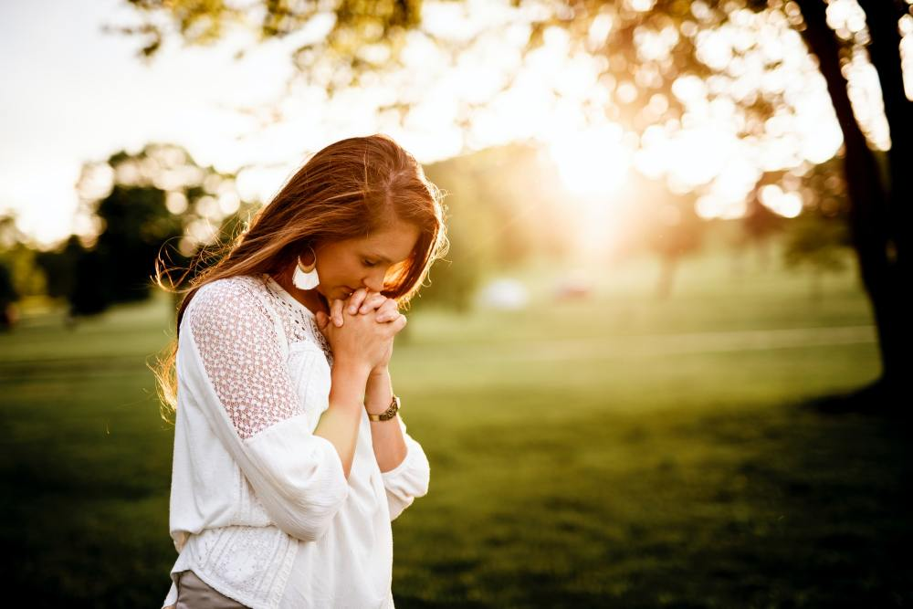 A woman with auburn hair and a white blouse with her head bowed down and her hands clasped together near her mouth in prayer and a grassy field with some trees and sunlight in the background