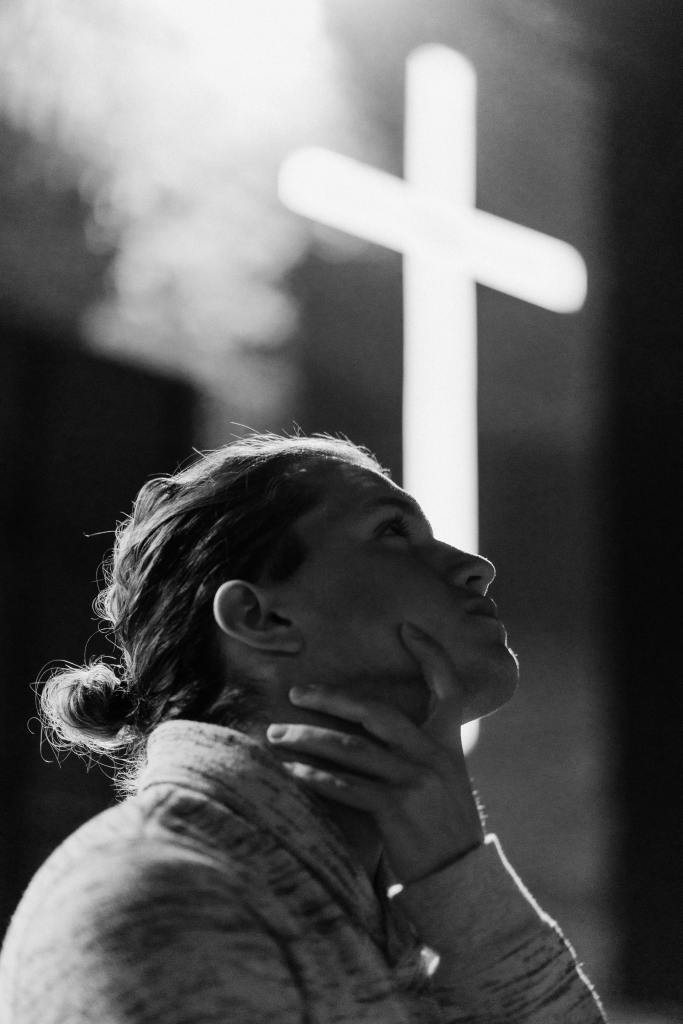 A black and white photo of a woman with hand resting around neck looking up in contemplation with a blurred white cross in the background