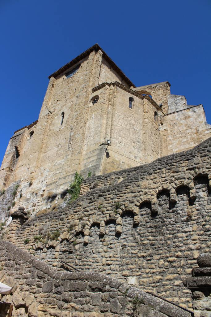A large old stone building sitting on a high elevation with a decorative stone wall and stairway leading up to it and a deep blue sky in the background