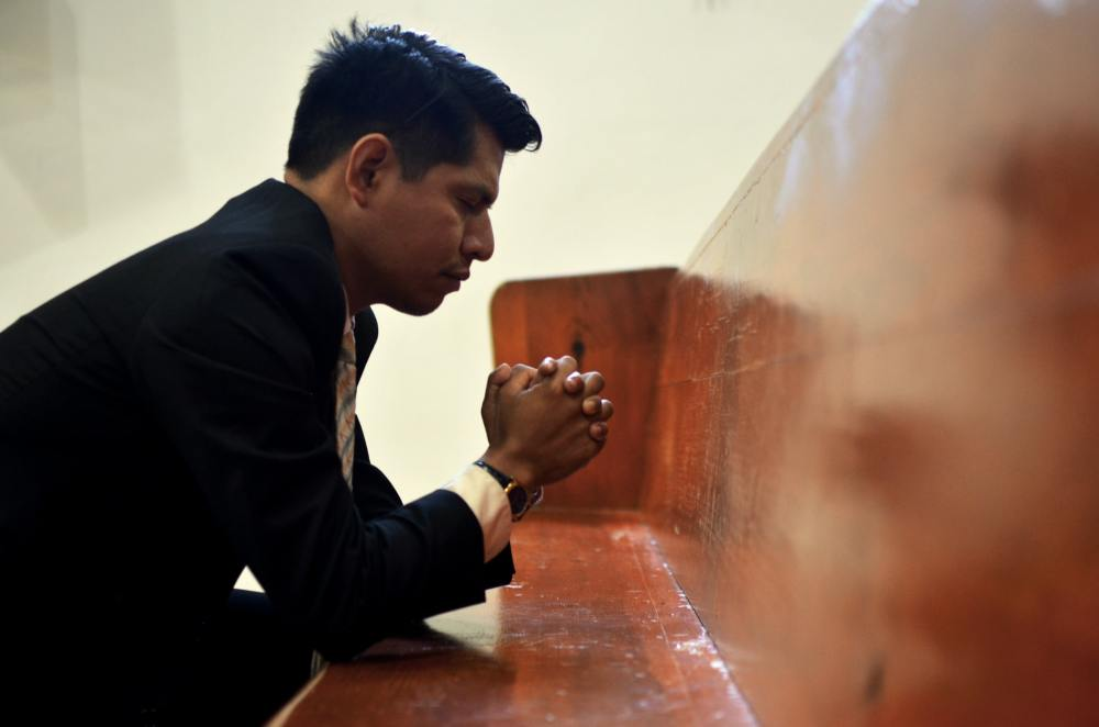 A photo of an Asian man kneeling against a wooden pew with his hands folded and eyes closed in prayer