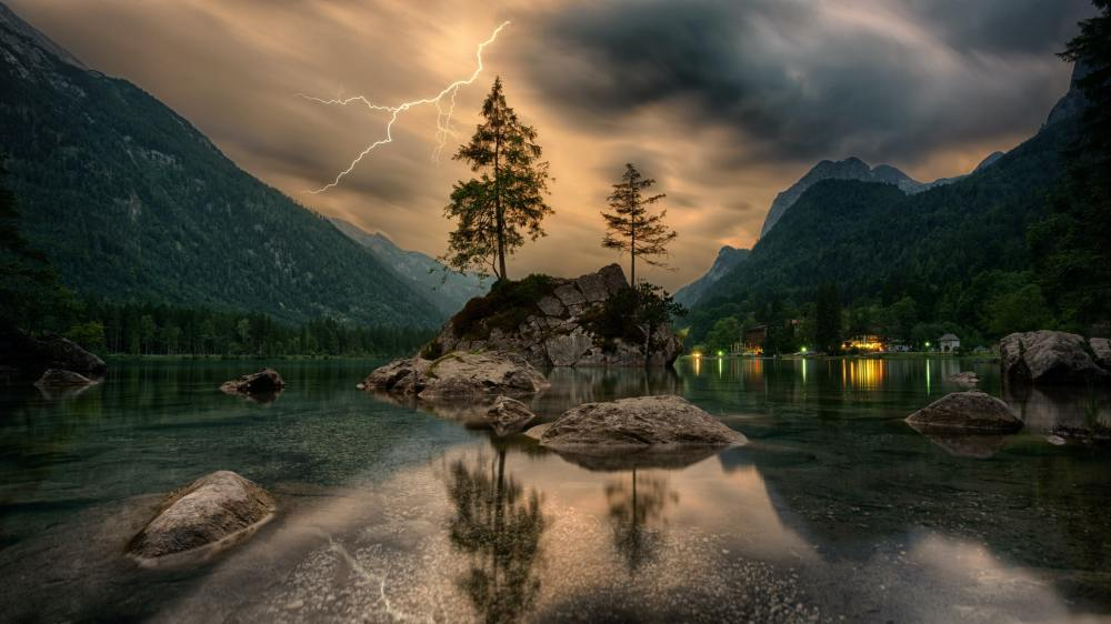 A photo of a calm lake with large mountains, dark clouds, lightning, two tall coniferous trees and an orange sky in the background