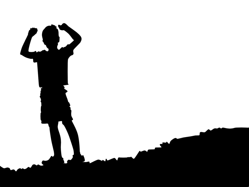 A black and white graphical image of a silhouette of a boy on the left side of the image wear shorts and t-shirt with his arms raised in the air while standing on the lower part of a small incline