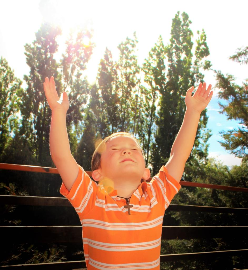 A young girl wearing an orange horizontally white striped shirt with arms raised and eyes closed