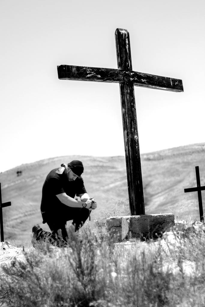 A black and white photo of a man dressed in black and wearing a black cap while kneeling at a large cross in a wilderness area and a large hill in the background