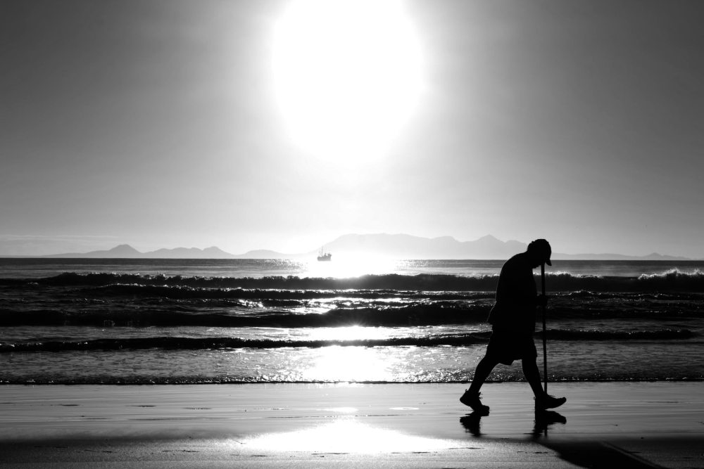 A black and white picture of a man walking on the beach with a bright sun near the horizon with a small vessel in the distance in the heart of the sun beam on the water