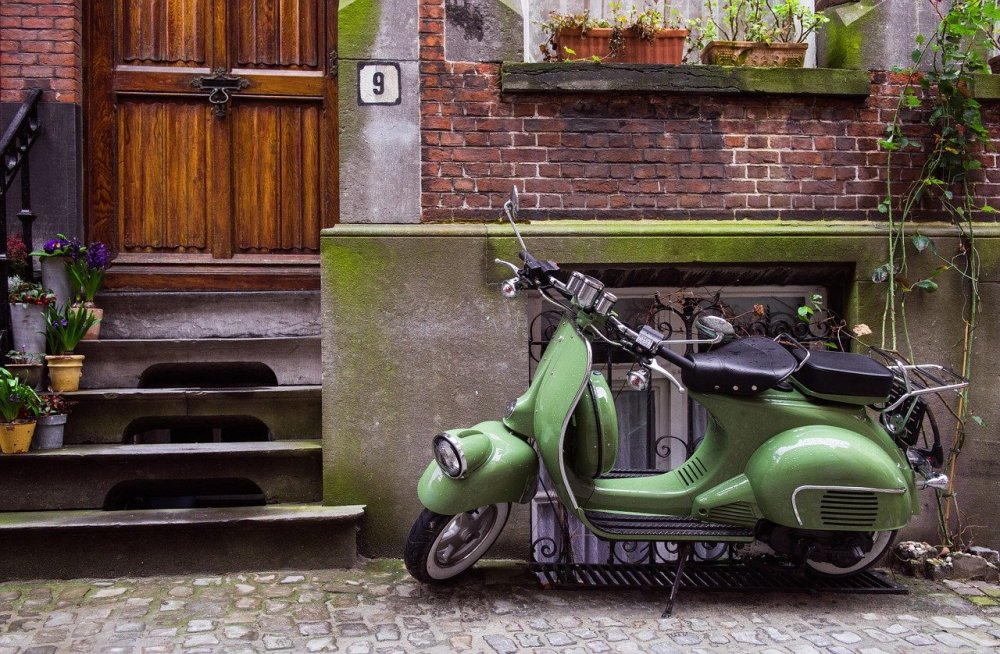 A photo of a green moped in front of the basement window of an old brick townhome with a stained wooden door and plants on the window sill
