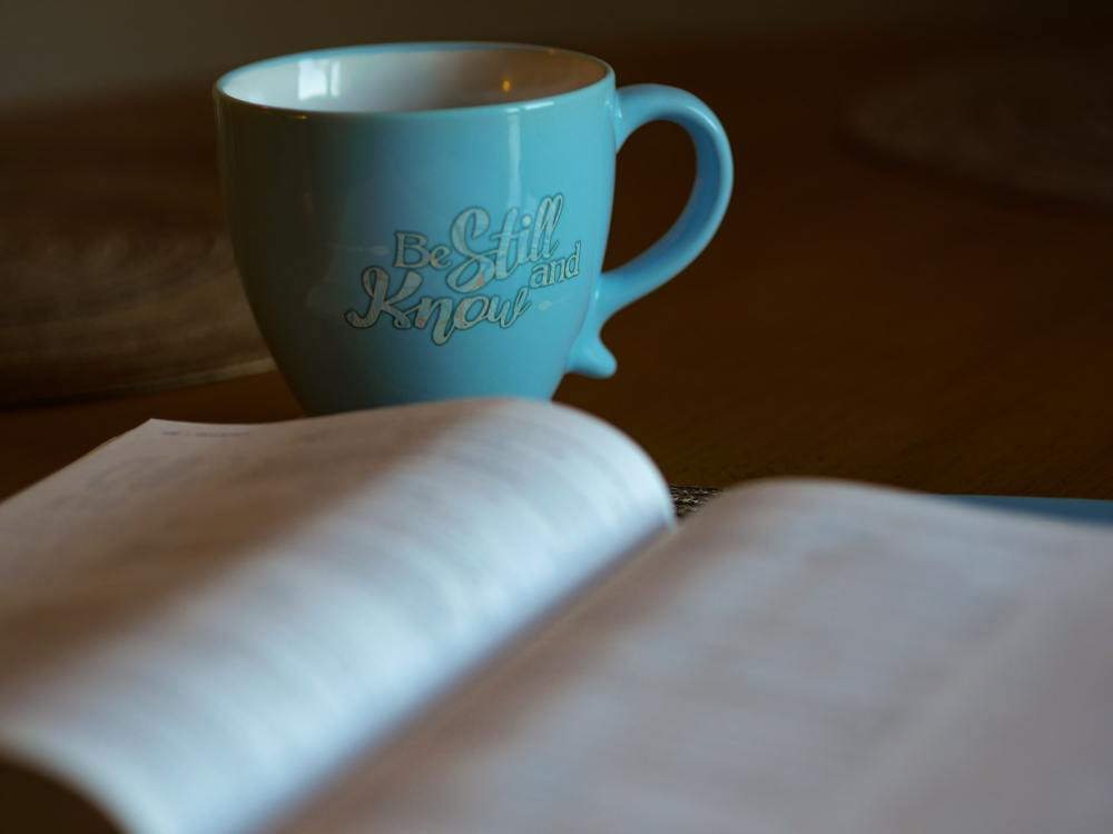 A photo of an open out of focus book lying flat on a table with a blue coffee cup immediately behind it