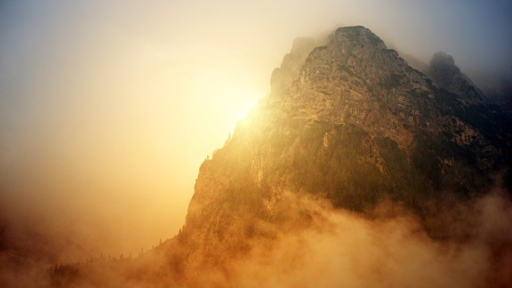 A large mountain with clouds below and a bright orange sun peering through the haze on the left side of it